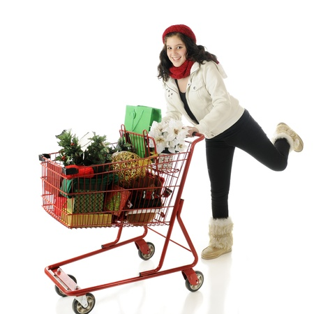 An attractive young teen running with a shapping cart filled with Christmas goodies.  On a white background. photo