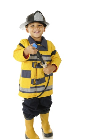 An adorable preschool fire chief in full gear.  Hes happily aiming his hose.  On a white background.
