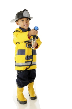 An adorable preschool in full Fire Chief gear aiming his hose toward a (pretend) fire.  On a white background.
