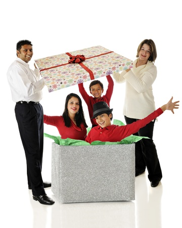 Biracial parents lifting the lid of a giant gift box to happily discover its filled with their three kids.  On a white background.
