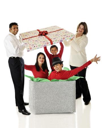 Biracial ouders optillen van het deksel van een gigantische doos om gelukkig te ontdekken zijn gevuld met hun drie kinderen. Op een witte achtergrond.