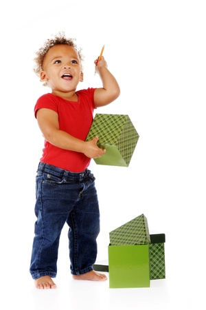 An adorable toddler happily playing with a pencil and gift boxes.  On a white background. photo