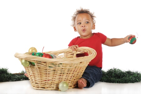 An adorable baby boy throwing a Christmas bulb taken from a basket of bulbs.  Motion blur on boy's hand and bulb.  On a white background. Stock Photo - 16168616