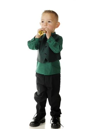An adorable, dressed up preschooler blowing his tiny gold trumpet.   On a white background.
