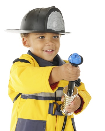 Closeup image of an adorable preschool Fire Chief aiming at a (pretend) fire with his water hose.  On a white background.