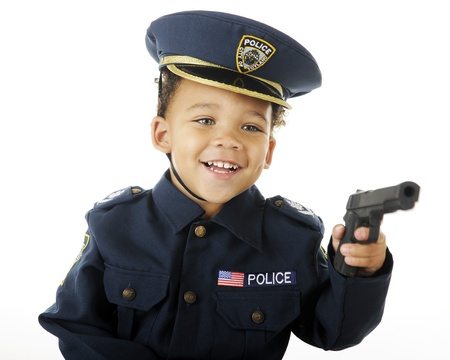Closeup image of an adorable preschool policeman happily aiming his gun.  On a white background. Stock Photo - 16168652