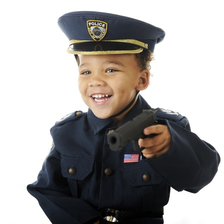 Closeup image of a delighted preschooler weilding a toy guy in his policeman uniform.  Motion blur on hand and gun.  On a white background. Stock Photo - 16168648