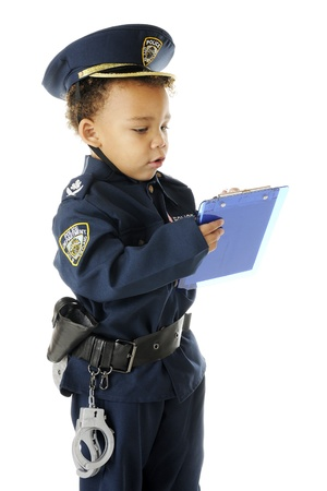 An adorable preschool police officer in full uniform writing a ticket.  On a white background. photo