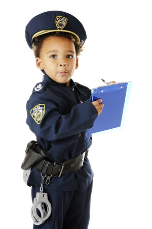 An adorable preschool policeman in uniform, looking up from writing a ticket.  On a white background. 스톡 콘텐츠
