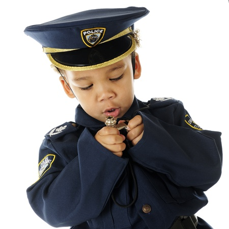 Closeup of an adorable preschool policeman in full uniform examining his two silver whistles.  On a white background. photo