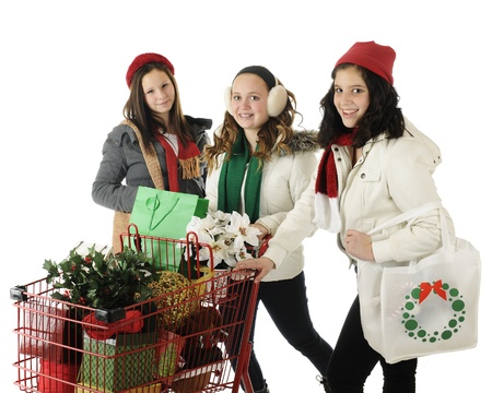 Three young teen friends happily filling their red shopping cart with Christmas goodies.  On a white background. Stock Photo - 16168650