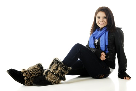 An attractive young teen sitting on the floor, happily relaxed in her jacket, scarf and furry boots.  On a white background.