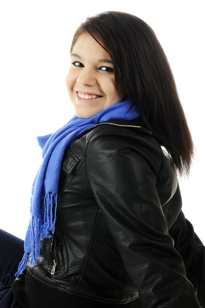 Closeup image of an attractive young teen happily looking over her shoulder.  She's wearing a dark leather jacket and blue neck scart.  On a white background. photo
