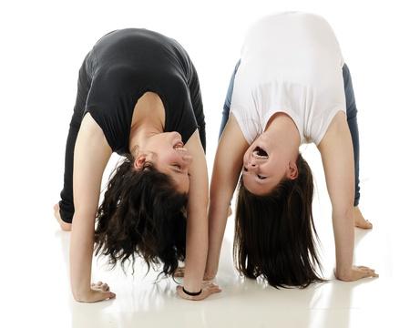 preadolescentes: Dos tween riendo mientras se miran unos a otros al rev�s en backbends mutuos. En un fondo blanco.