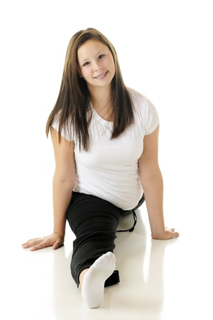 Front view of an attractive tween girl doing the splits.  On a white background. photo