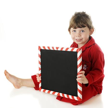 striped pajamas: Un ni�o en edad preescolar adorable descalzo en pijama rojo acogedoras feliz con un cartel marco multicolor pizarra. La muestra se deja en blanco para el texto. En un fondo blanco. Foto de archivo