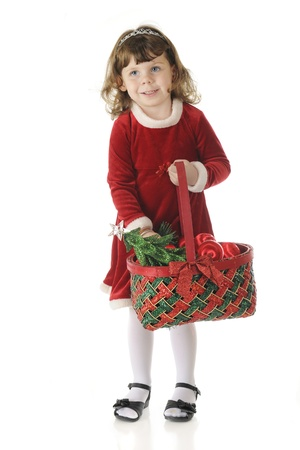 velvet dress: An adorable preschooler all dressed up for Christmas.  Shes happily carrying a basket filled with Christmas items.  On a white background.