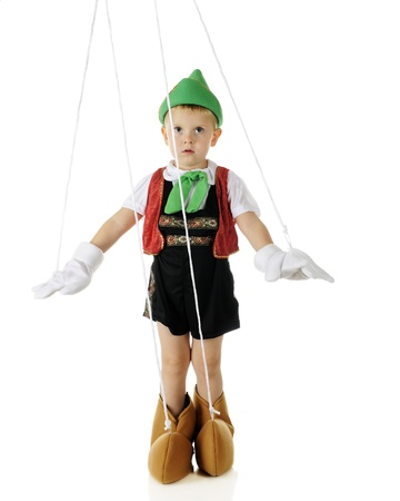 An adorable preschooler playing the puppet Pinocchio, strings and all.  On a white background. Stock Photo - 16168628