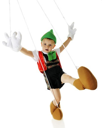 An adorable live preschool Pinocchio manette dancing, strings and all.  On a white background. Stock Photo - 16168632