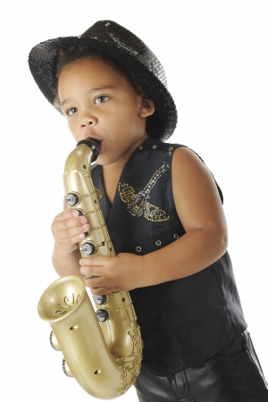 An adorable preschooler playing a toy saxophone in a sparkly black fedora and balck leather vest and pants.  On a white background. Stock Photo - 16366730