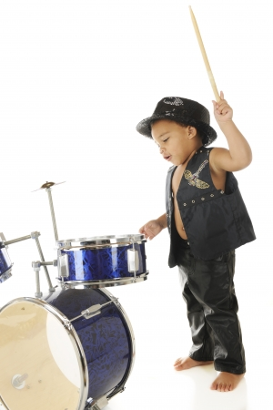 leather pants: An adorable, barefoot preschooler dressed as a rock star with a drum stick poised high over a drum set, ready to wham it.  On a white background.