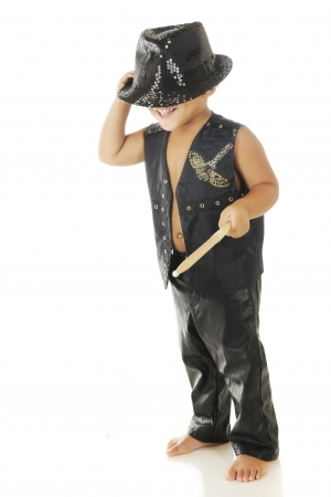 A happy, barefoot preschooler in black leather vest and pants with a sparkly fedora covering his eyes.  On a white background. Stock Photo - 16366782