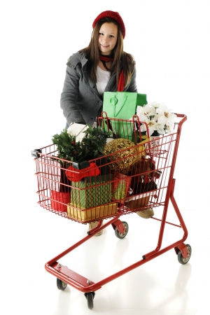 An attractive tween girl leaning on a red shopping cart filled with Christmas goodies.  On a white background. Stock Photo - 16366789
