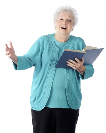hymn: An attractive senior woman happily singing from a book.  On a white background. Stock Photo