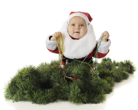 An adorable baby Santa happily clutching strands of Christmas beads while sitting surrounded by green garland.  On a white background.