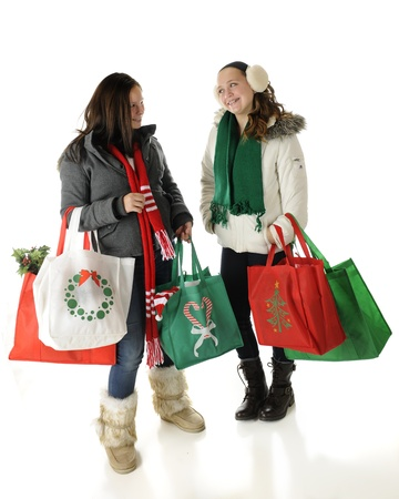 Two preteens meet and talk while Christmas shopping.  On a white background. Imagens