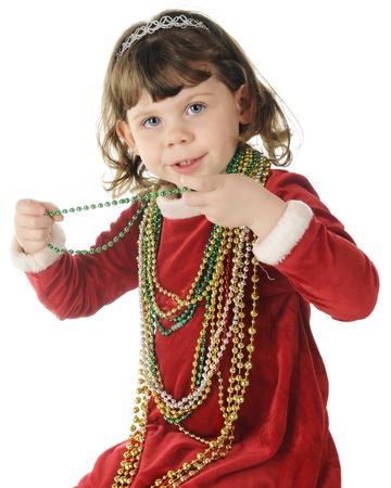 velvet dress: An adorable preschooler in her red velvet Christmas dress happily wearing oodles of Christmas beads.  On a white background.