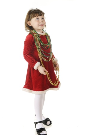 velvet dress: An adorable preschooler in a red velvet dress with multiple strands of colored beads around her neck.  Shes looking up with the wonder of Christmas.  On a white background.  Stock Photo