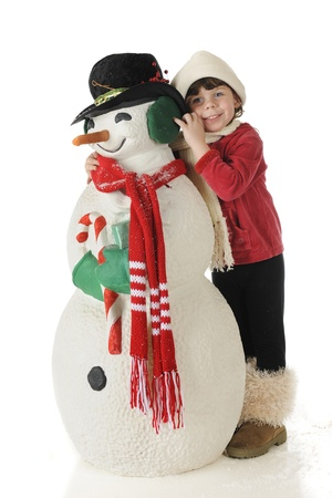 snuggling: An adorable preschooler in outside winter wear snuggling up with a snowman dressed for Christmas.  On a white background. Stock Photo