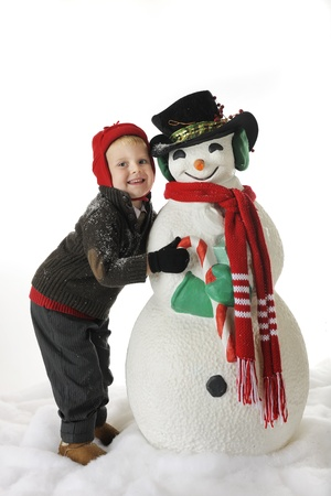 An adorable preschool boy in winter clothes and a dusting of snow posing with a snowman decked out for Christmas.  On a white background. photo