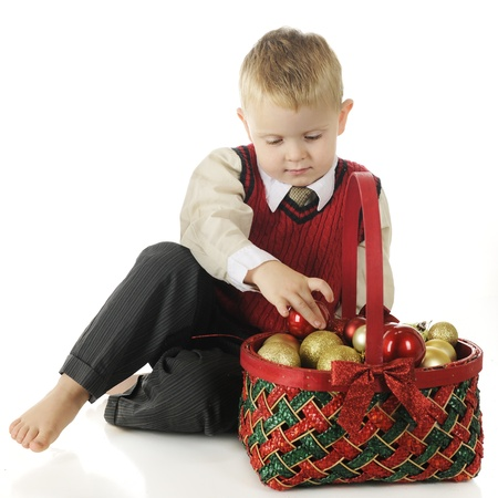 A dressed up but barefoot preschool boy taking Christmas bulbs from a red and green basket.  On a white background. Stock Photo - 16496108
