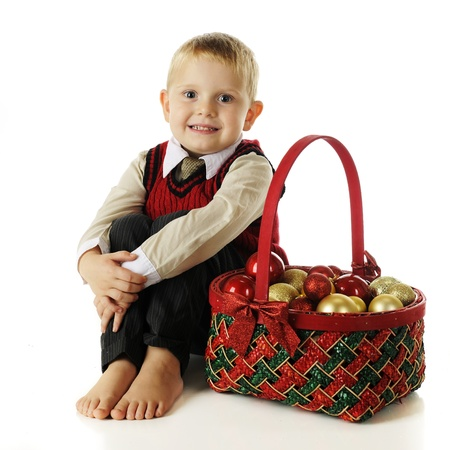 A barefoot preschooler in casual dress-clothes happily sitting by a red and green basket filled with Christmas bulbs.  On a white background. Stock Photo - 16496096