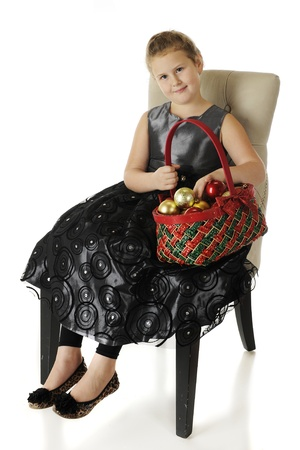 dressy: A happy elementary girl sitting in a dressy black dress while holding a red and green basket filled with ornaments.  On a white background.