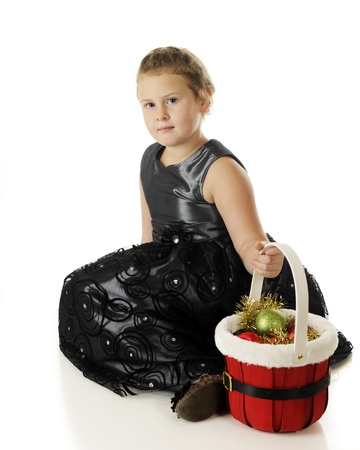 A pretty elementary girll dressed up in black and sitting with a red basket filled with ornaments.  On a white background. Stock Photo - 16496109