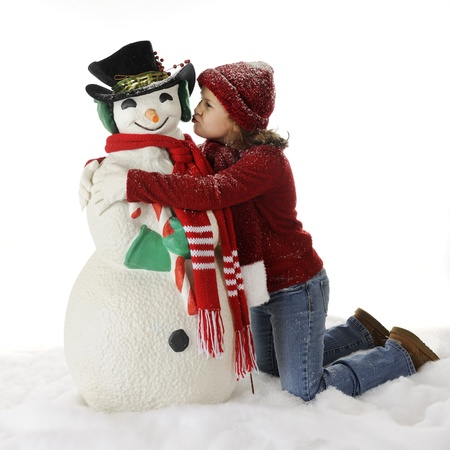 An elementary girl kneeling in the snow to kiss her Christmasy snowman.  On a white background. photo