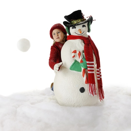 An elementary girl tosses a snowball from behind a Christmasy Ssnowman.  Motion blur on snowball.  On a white background.