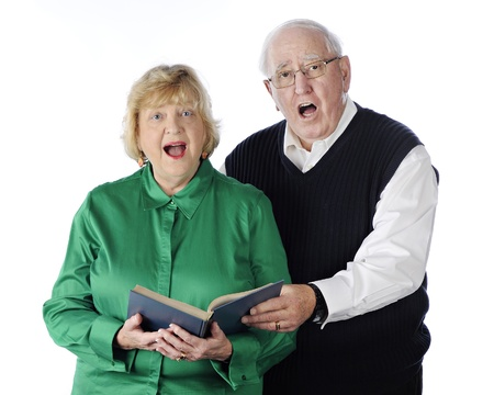 sings: A senior adult couple singing praises together from a hymnal.  On a white background.