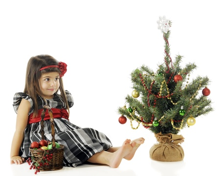 An adorable preschooler sitting back to contemplate the decorations on her own tiny Christmas tree.  On a white background. Stock Photo - 16621456