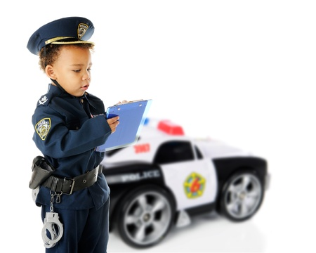 An adorable preschool policeman in full uniform writing a traffic ticket.  His policecar is visible in the background.  On a white background.