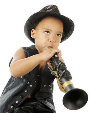 A biracial preschooler playing a clarinet in a sparkly black fedora and black leather vest.  On a white background. Stock Photo - 16621453