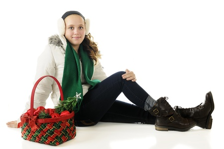 jeans girl: An attractive preteen sitting in winter wear with a Christmas basket filled with ornaments.  On a white background. Stock Photo