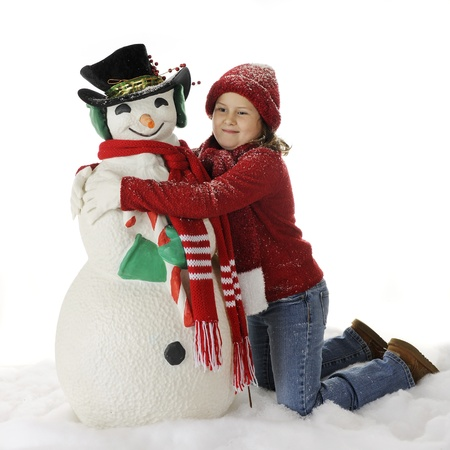 An elementary girl giving her Christmasy snowman a hug.  On a white background. photo