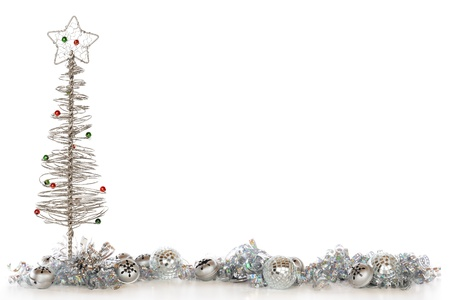 A border composed of a wire Christmas tree, bells, shimmery bulbs and curly ribbon, all in sliver.   Isolated on white with plenty of room for your text. Stock Photo - 16512938