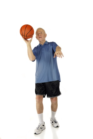 A senior man preparing to shoot a basketball with one hand   On a white background  photo