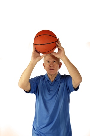 Senior man setting up to shoot a basketball   On a white background  photo