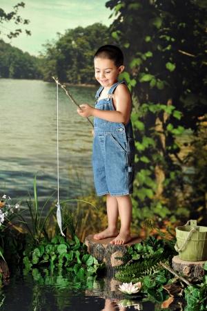 piedi nudi ragazzo: Un giovane, a piedi nudi ragazzo felice quando cattura il suo primo pesce. Archivio Fotografico